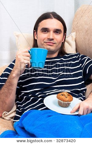 Man Having Breakfast On Sofa