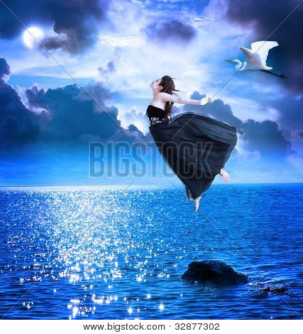Beautiful Girl Jumping Into The Blue Night Sky