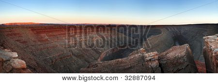 Dramatic panorama of Gooseneck Canyon at dusk. The Colorado river snakes though the landscape in Utah, USA.
