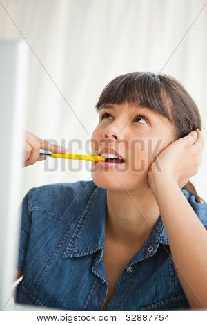 Student looks up while grimacing and chewing a pencil