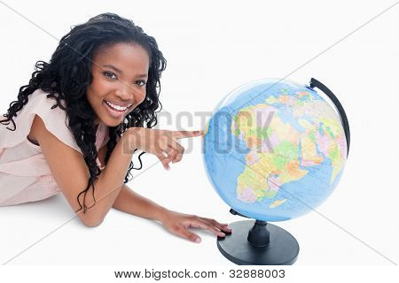 A young smiling girl is looking at the camera with her finger on a globe against a white background