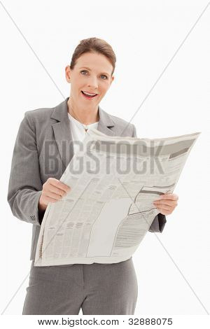 A surprised businesswoman is holding a newspaper