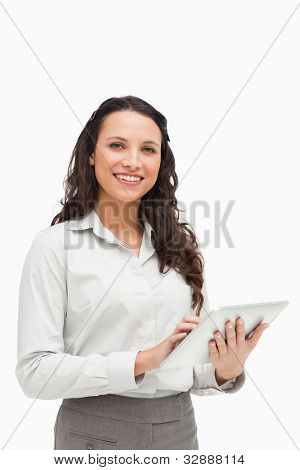 Portrait of a brunette standing while using a touchpad against white background
