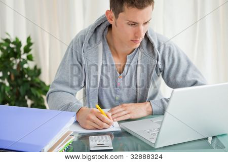 Student doing his homework with a laptop at his desk