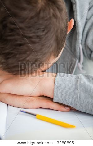 Close-up of a student head on his desk doing his homework