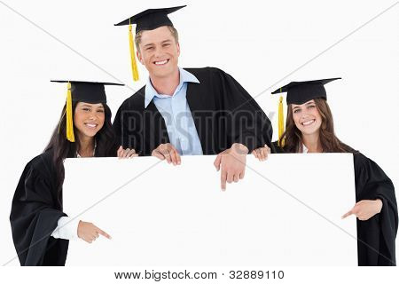 Three graduates pointing to the blank sign while smiling and looking at the camera