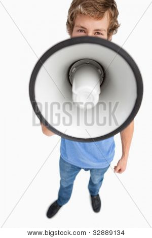 Fisheye view of a male student speaking in a megaphone against white background