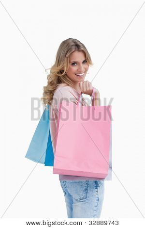 A woman who is carrying shopping bags is smiling at the camera