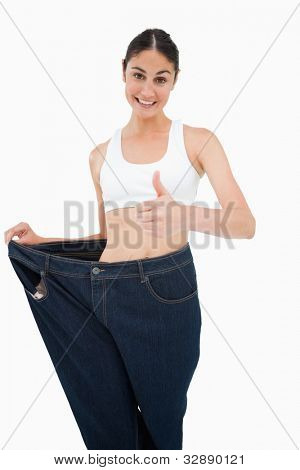 Smiling woman who lost a lot of weight the thumb-up against white background