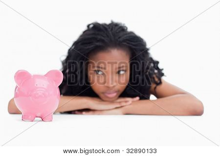 A young woman is lying down on the floor resting her head on her hands looking at a piggy bank