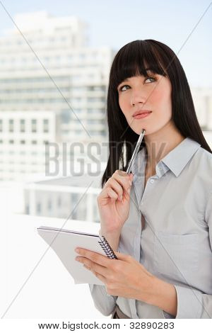 A woman in her office with a notepad and a pen against her chin looks upwards as she thinks