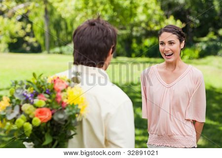Woman excited as she approaches her friend who has flowers hidden behind his back