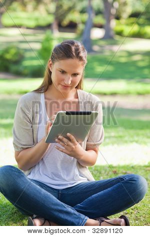 Young woman sitting on the grass while using her tablet computer