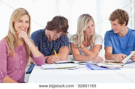 A study group working hard as one girl smiles and looks at the camera with her hand on her chin in a thinking expression
