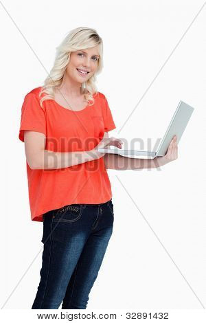 Smiling and beautiful woman looking at the camera while holding a new laptop