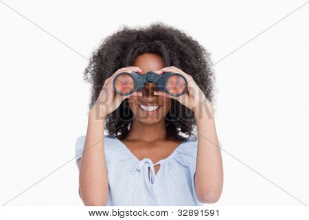 Young woman with curly hair looking through binoculars against a white background