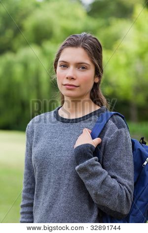 Young girl looking straight at the camera while standing upright in the countryside