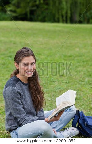 Young smiling girl sitting cross-legged on the grass while holding a book in a park