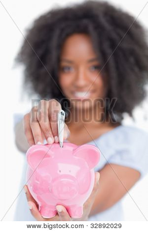 Young woman inserting notes in a piggy bank against a white background