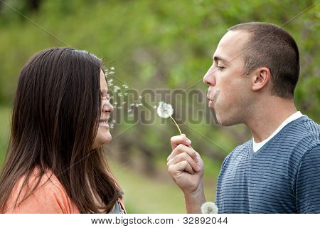 Young Couple Blowing Dandelions