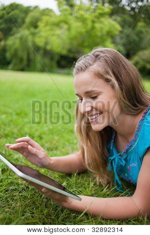 Young happy woman using her tablet pc while lying on the grass in a public garden