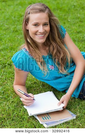 Young smiling girl looking at the camera while lying on the grass in the countryside