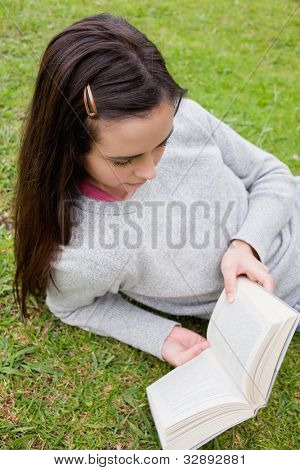 Young serious woman reading a book while lying down in a public garden