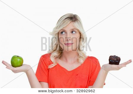 Woman holding a chocolate muffin and a green apple