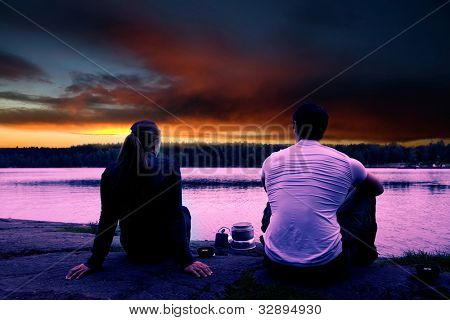 A couple watching the sunset while camping by a lake