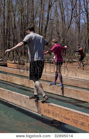 POCONO MANOR, PA - APR 29: Participants walk across a narrow beam over water at Tough Mudder on April 29, 2012 in Pocono Manor, Pennsylvania. The course is designed by British Royal troops.