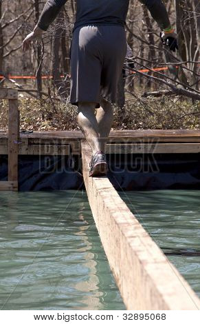 POCONO MANOR, PA - APR 29: A man walks across a narrow beam over water at Tough Mudder on April 29, 2012 in Pocono Manor, Pennsylvania. The course is designed by British Royal troops.