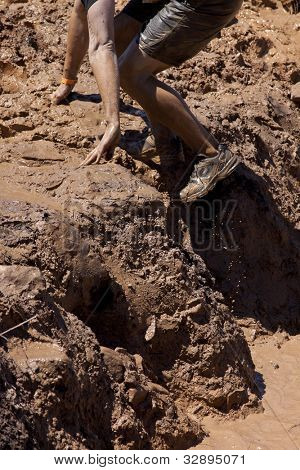 POCONO MANOR, PA - APR 29: A man climbs out of a pit of mud and water at Tough Mudder on April 29, 2012 in Pocono Manor, Pennsylvania. The course is designed by British Royal troops.