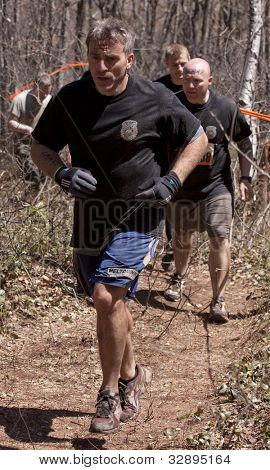 POCONO MANOR, PA - APR 29: A group of men run on a trail through the woods at Tough Mudder on April 29, 2012 in Pocono Manor, Pennsylvania. The course is designed by British Royal troops.