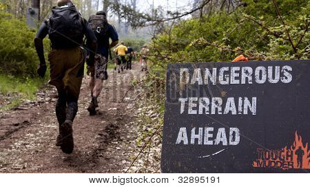 POCONO MANOR, PA - APR 28: Participants run past a sign that reads Dangerous Terrain Ahead  at Tough Mudder on April 28, 2012 in Pocono Manor, Pennsylvania. British Royal troops designed the course.