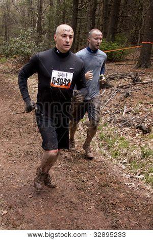 POCONO MANOR, PA - 28 de abr: Dois homens executados em uma trilha pela floresta em Mudder resistente em 28 de abril de 201