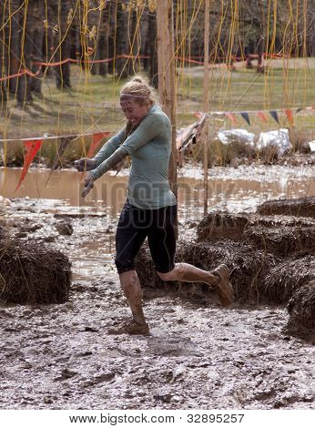 POCONO MANOR, PA - APR 28: A woman runs through an obstacle with electrified wires at Tough Mudder on April 28, 2012 in Pocono Manor, Pennsylvania. The course is designed by British Royal troops.