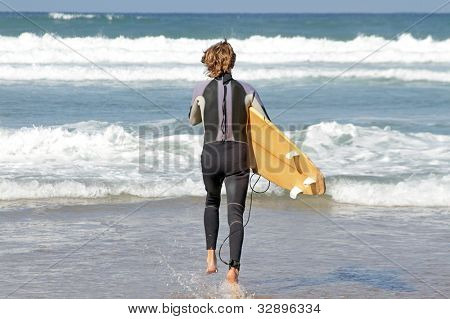 Young guy is going to surf in the atlantic ocean
