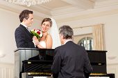 stock photo of waltzing  - Bridal couple in front of a piano - JPG