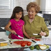 Hispanic grandmother and granddaughter preparing food