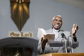stock photo of piety  - African American Reverend preaching in church - JPG