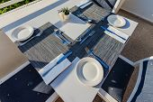Table Set With Dishes For Dinner On The Veranda. The Table Is Set With Dishes And Cutlery For Dinner poster