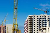 Construction Cranes On The Background Of Multi-apartment Buildings Under Construction. The Concept O poster