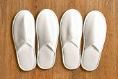 Top View Two Pairs Of New Soft White Slipper In The Hotel On Wooden Floor. Four White Slipper, Isola poster