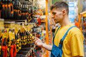 Male builder choosing pliers in hardware store poster