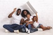 Mortgage For Young Families. Happy Black Parents And Their Two Kids Sitting Under Symbolic Roof Drea poster