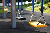 stock photo of swingset  - Black and yellow empty playground swings in a row