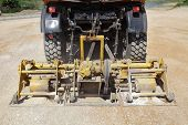 stock photo of vibration plate  - Road compactor tool compacting gravel at road construction site - JPG