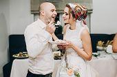 Bride And Groom Tasting Stylish Wedding Cake At Wedding Reception In Restaurant. Wedding Couple Plat poster