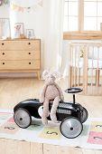 Plush Rabbit Is Sitting In Vintage Racing Children Car In Children Room. Scandinavian Style Interior poster