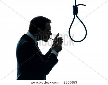 one caucasian man smoking cigarette  standing in front of hangman's noose in silhouette studio isolated on white background